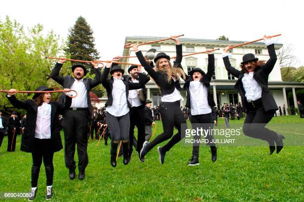 People dressed as 'The Tramp' jump in the air for a photograph part of celebrations to mark the first anniversary of Chaplins World By Grevin and...