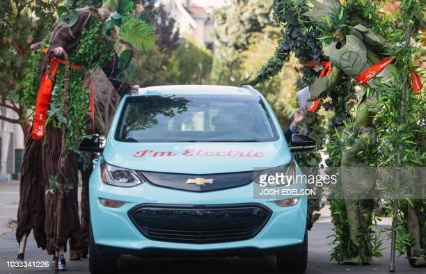 People dressed as trees hand a letter to a driver in an electric car who will travel across the county to New York City to hand deliver it to the...