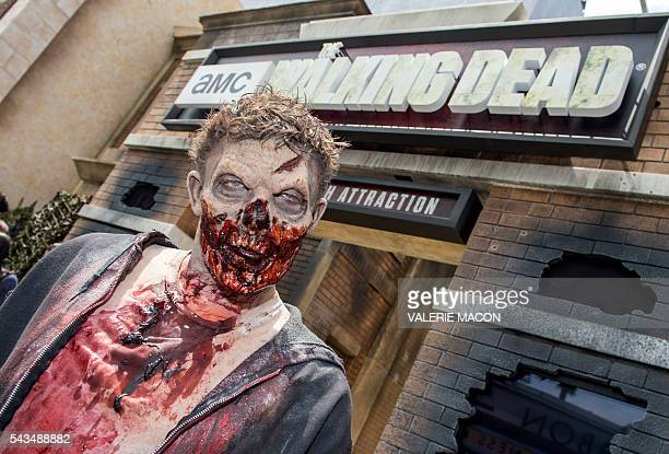 People dressed as zombies act for the camera at the Universal Studios Hollywood Opening of its New Permanent Daytime Attraction The Walking Dead in...