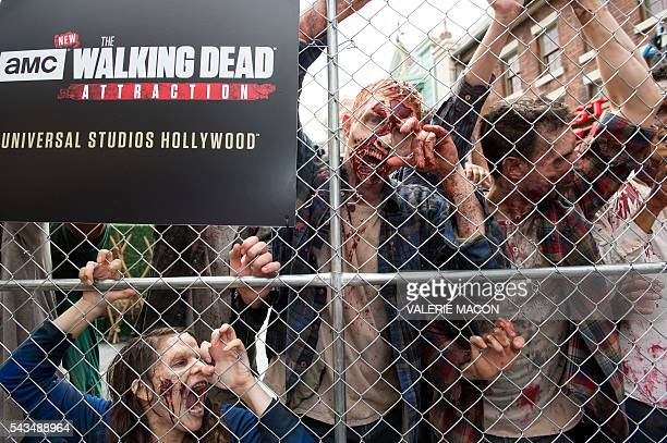 People dressed as zombies push on a fence at the Universal Studios Hollywood Opening of its New Permanent Daytime Attraction The Walking Dead in...