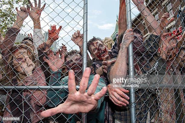 People dressed as zombies push onto a fence at the Universal Studios Hollywood Opening of its New Permanent Daytime Attraction The Walking Dead in...