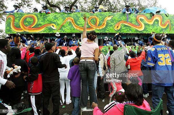 People dressed in blackface toss beads to the crowd during the Zulu parade a primarily AfricanAmerican parade during Mardi Gras festivities February...
