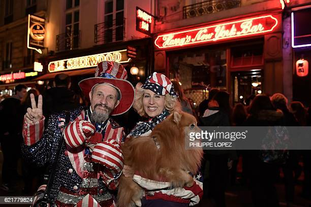 People dressed in colours of the US national flag pose outside the Harry's New York Bar in Paris on November 8 2016 where a straw vote for US...