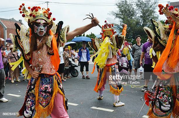 People Dressed In Costume Dancing On Street During Traditional Festival