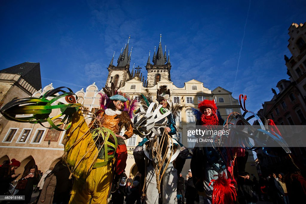 People dressed in costume sit on giant carnival figures during the opening of the Carnevale Praga 2015 festival as part of Prague carnival season at the Old Town Square on February 7, 2015 in Prague, Czech Republic. Carnivals start across Czech Republic and celebrate the departing winter, forthcoming spring and start of forty-day Lent.