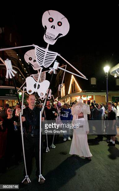 People dressed in costume walk down Bourbon Street with the Storyville Stompers brass band during Jim Monaghan's Annual Halloween Parade through the...