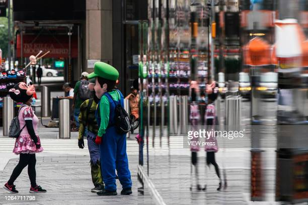 People dressed in costumes as they wait for tourist in Times Square on August 8 2020 in New York City With more than four months NYC has closed some...