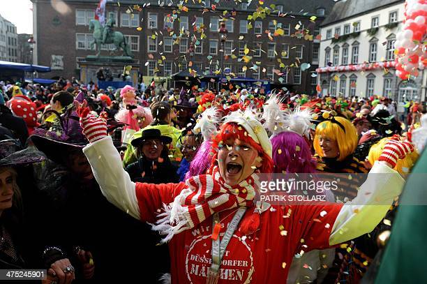 People dressed in costumes celebrate the traditional 'Weiberfastnacht' women's carnival in Duesseldorf western Germany on February 27 as the hot...