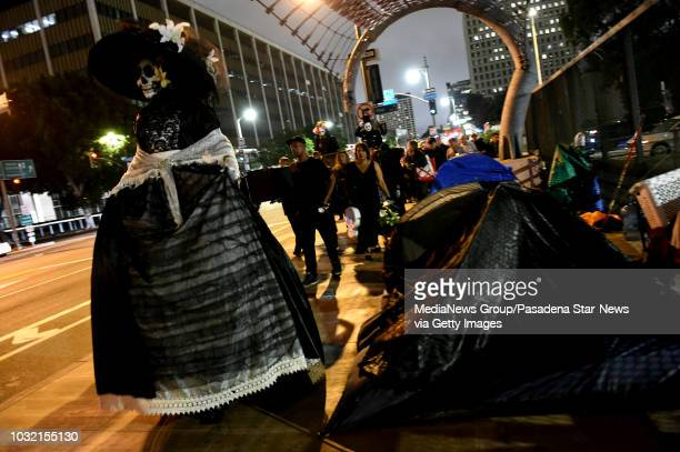People dressed in costumes march past homeless tents during a housing and homeless advocates funeral procession and Candlelight March to mourn the...