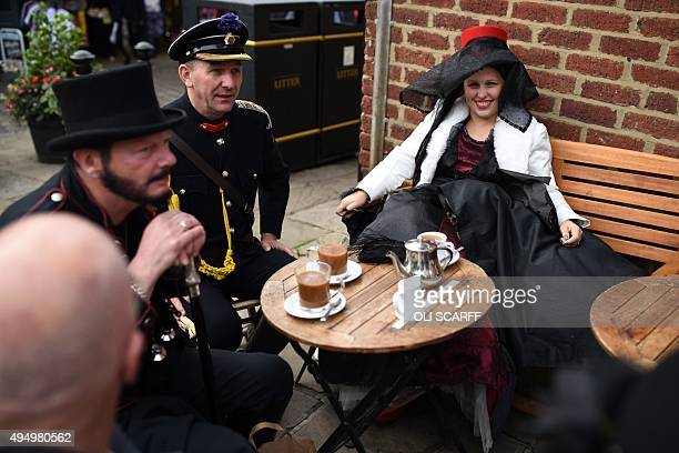 People dressed in costumes sit at a cafe terrace during the biannual Whitby Goth Weekend festival in Whitby northern England on October 30 2015 The...
