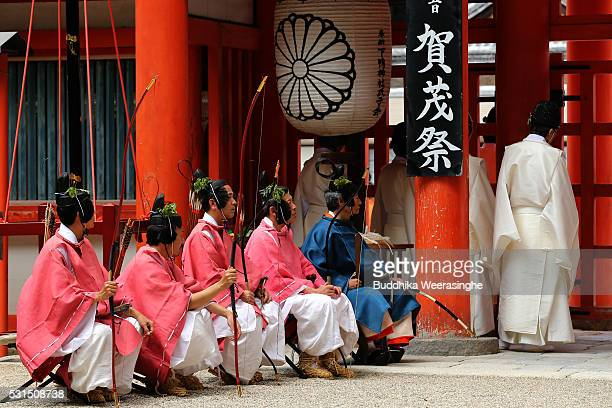 People dressed in Heian Period costumes sit front of the shrine gate during the Aoi Festival at Shimogamo Shrine on May 152016 in Kyoto Japan Aoi...