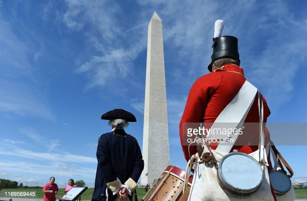 People dressed in historical costumes participate in the reopening of the Washington Monument on the National Mall on September 19 2019 in Washington...