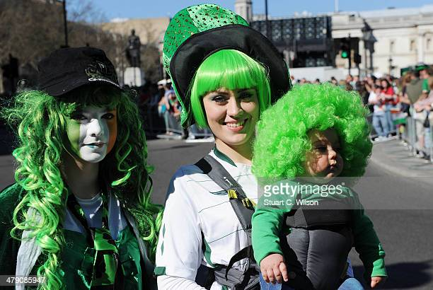 People dressed in Irish themed costumes watch the annual St Patrick's Day Festival pass from Piccadilly to Trafalgar Square through Haymarket on...