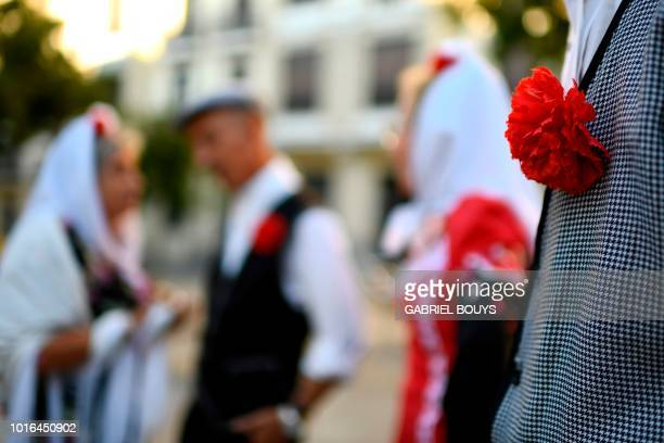 People dressed in Madrid's traditional attire Chulapos attend the Feast of La Paloma Virgin in Madrid on August 13 2018 Madrid's history and...
