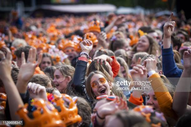 People dressed in orange dance as they attend a concert of 538 radio's DJs to celebrate Koningsdag - King's Day, on the day of Dutch King...