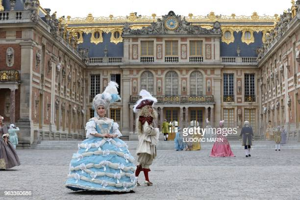 TOPSHOT People dressed in period costumes pose for a photograph during the Fetes Galantes fancy dress evening in front of the Chateau de Versailles...