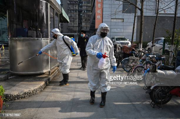 TOPSHOT People dressed in protective clothes disinfect an area in Wuhan in Hubei province on January 30 2020 The World Health Organization which...