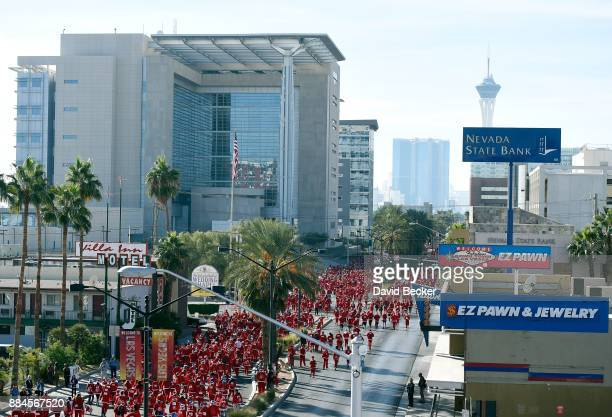 People dressed in Santa Claus costumes participate in the 13th annual Las Vegas Great Santa Run benefiting Opportunity Village at the Fremont Street...
