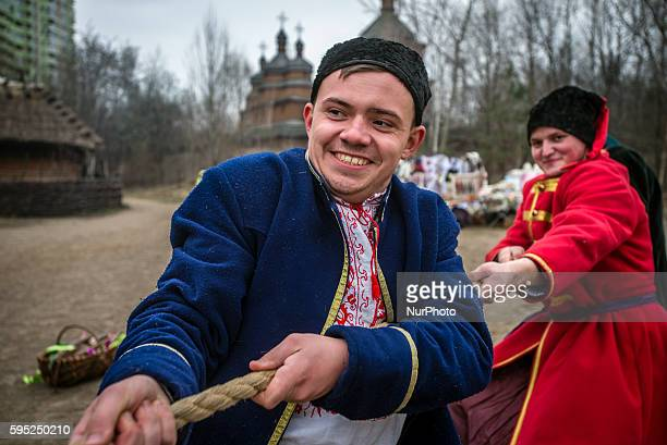 People dressed in the traditional costumes celebrate Maslenitsa in Ukrainian rites in Mamayeva Sloboda Kyiv Ukraine on March 13 2016