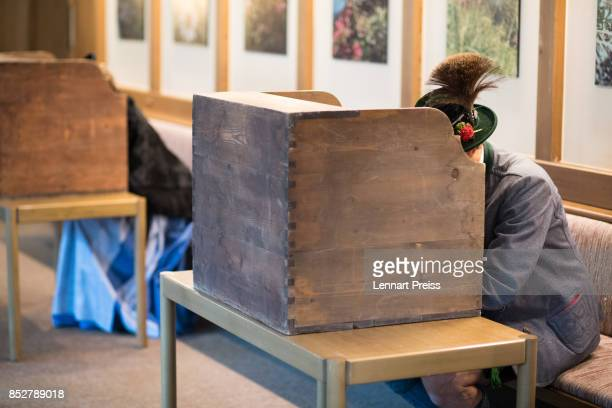 People dressed in traditional Bavarian clothes sit behind voting booths as they fill in their election ballots at a polling station during German...