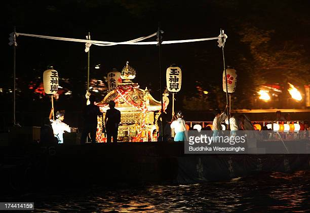 People dressed in traditional costume carry portable shrine by boat along the Okawa river during the annual Tenjin summer festival boat parade on...