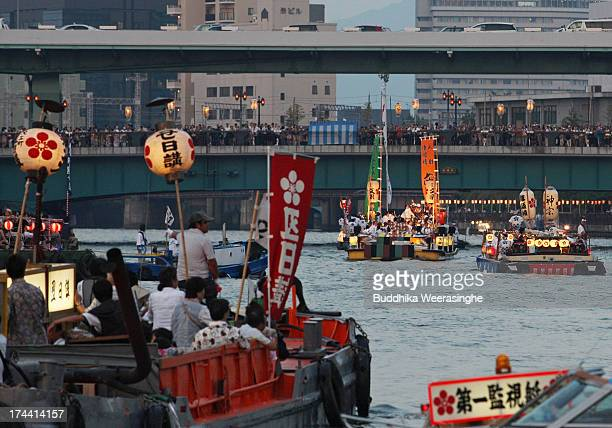 People dressed in traditional costume ride decorated ferries along the Okawa river during the annual Tenjin summer festival boat parade on July 25...