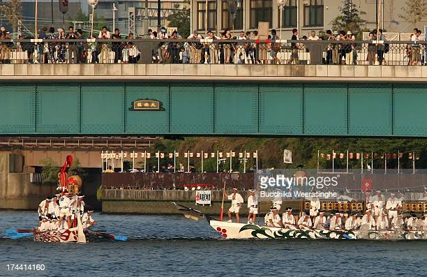 People dressed in traditional costume row boats along the Okawa river during the annual Tenjin summer festival boat parade on July 25 2013 in Osaka...