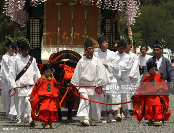 People dressed in traditional costumes draw a cow carriage in the procession of the Aoi Festival at the Imperial Palace on May 15 2013 in Kyoto Japan...