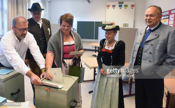 People dressed in typical Bavarian clothes cast their votes for regional elections in Bavaria at a polling station in Neukirchen southern Germany on...