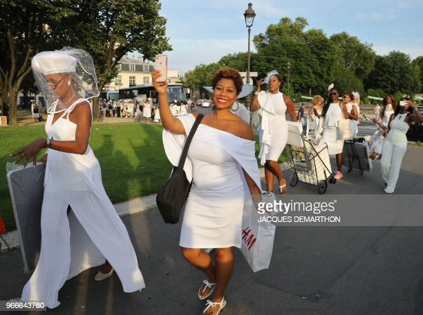 """People dressed in white arrive for a diner during the 30th edition of the """"Diner en Blanc"""" event on the Invalides esplanade in Paris on June 3, 2018...."""