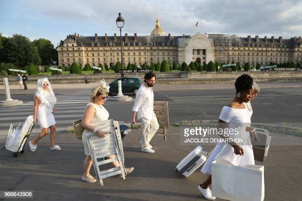People dressed in white arrive for a diner during the 30th edition of the 'Diner en Blanc' event on the Invalides esplanade in Paris on June 3 2018...