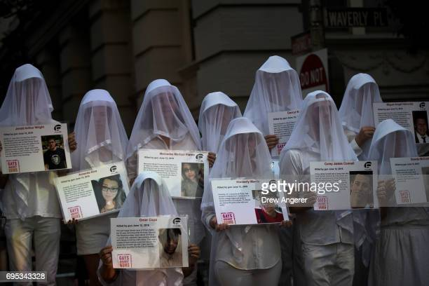 People dressed in white hold photos of victims from the 2016 Pulse nightclub shooting during a memorial service and rally down the street from the...