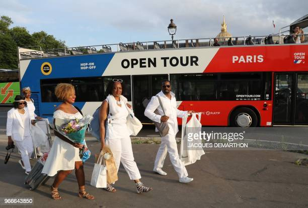 """People dressed in white pass by a Parisian guided tour bus as they arrive for a diner during the 30th edition of the """"Diner en Blanc"""" event on the..."""