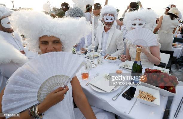 People dressed in white share a diner during the 30th edition of the 'Diner en Blanc' event on the Invalides esplanade in Paris on June 3 2018 with...