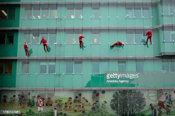 People dressed up as Santa Claus climb the wall of a pediatric clinic to entertain the children amidst coronavirus pandemic in Ljubljana, Slovenia on...
