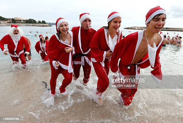 People dressed up as Santa Claus enjoy a traditional Christmas bath on December 23 2012 in Monaco AFP PHOTO / VALERY HACHE