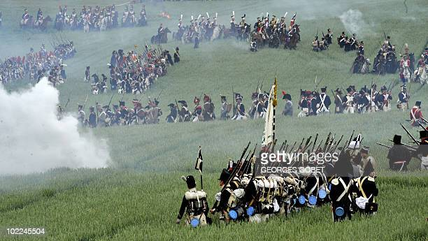 People dressed up as soldiers fight during a reenactment of the 1815 Battle of Waterloo between the French army led by Napoleon and the Allied armies...