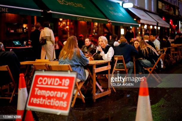 People drink at the outside tables of a cafe in Soho, in central London on September 23, 2020. - Britain on Tuesday tightened restrictions to stem a...