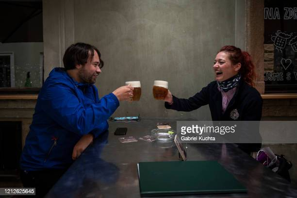 People drink beer at an outdoor seating section of a pub, as the Czech government lifted more restrictions allowing restaurants with outdoor areas to...