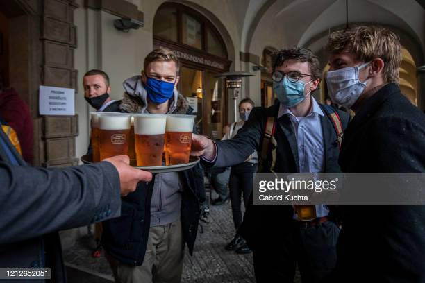People drink beer at an outdoor seating section of a pub as the Czech government lifted more restrictions allowing restaurants with outdoor areas to...