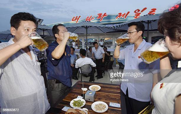 People drink beer during North Korea's first beer festival which started in Pyongyang on Aug 12 in line with its leader Kim Jong Un's promise to...