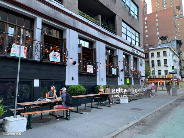 People drink cocktails outside a restaurant during the coronavirus pandemic on May 2, 2020 in New York City. COVID-19 has spread to most countries...