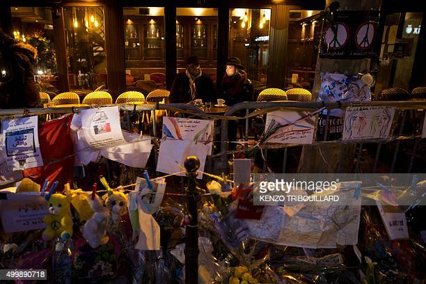 People drink coffee on the terrace of the bar A la Bonne Biere during its reopening in Paris on December 4 behind a barrier with flowers notes and...