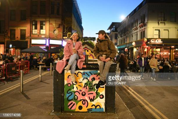 People drink coffees in the street outside the bars in the Northern Quarter of central Manchester, on April 12, 2021 as coronavirus restrictions are...
