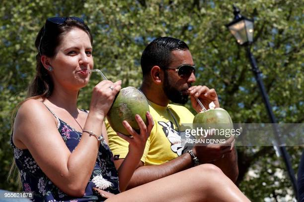 People drink from coconuts as they sit on the bank of the River Thames and soak up the sun in Richmond south west London on May 7 2018 Temperatures...