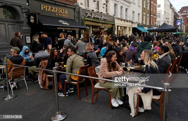People drink in the street in the Soho area of London, on April 16, 2021 following step two of the government's roadmap out of England's third...