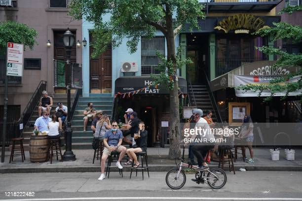People drink outdoor at bars and restaurants in the Hells Kitchen neighborhood of New York on June 7, 2020. - This week New York will enter phase one...