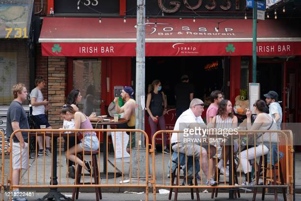 People drink outdoors at bars and restaurants in the Hells Kitchen neighborhood of New York on June 7, 2020. - This week New York will enter phase...