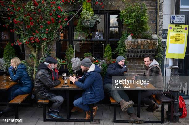 People drink outside a pub after it re-opened due to the change in lockdown restrictions on April 12, 2021 in Windsor, United Kingdom. England has...
