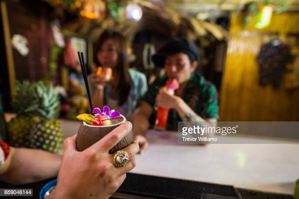 People drinking and enjoying themselves in a tropical themed restaurant or bar